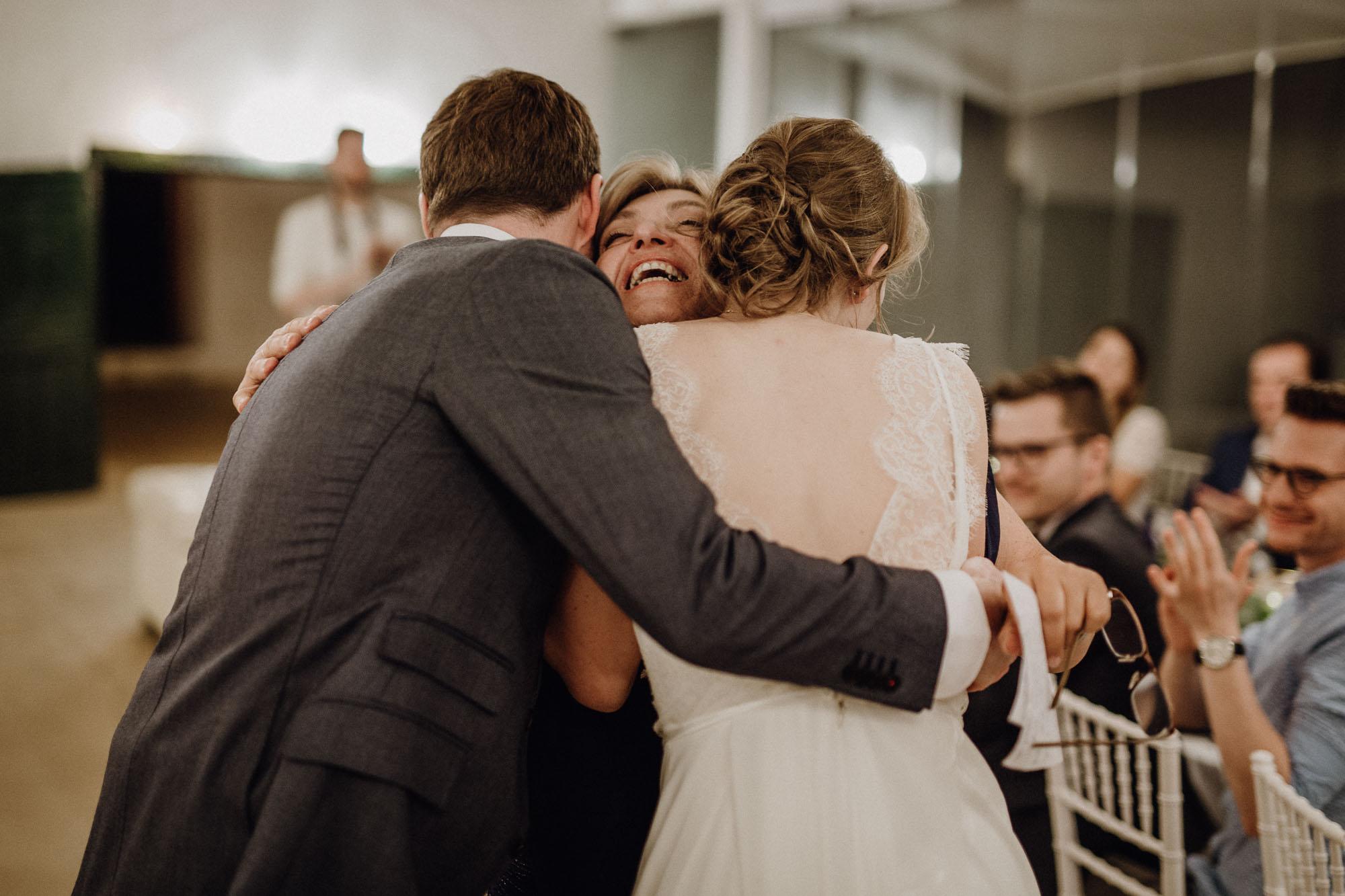Mutter umarmt das Brautpaar