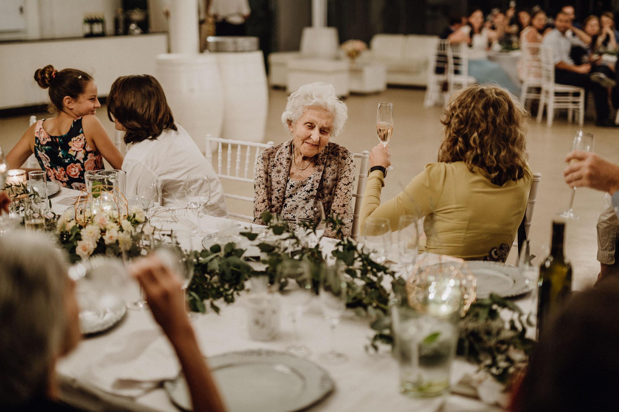 Die Oma sitzt lächelnd am Tisch