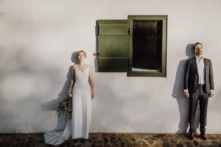Hochzeitsfotografie by Raissa + Simon. Brautpaar lehnt mit geschlossenen Augen an der Hauswand.