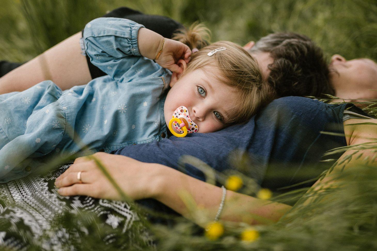 Familienfotografie by Raissa + Simon Fotografie. Kind liegt mit Eltern auf der Wiese.