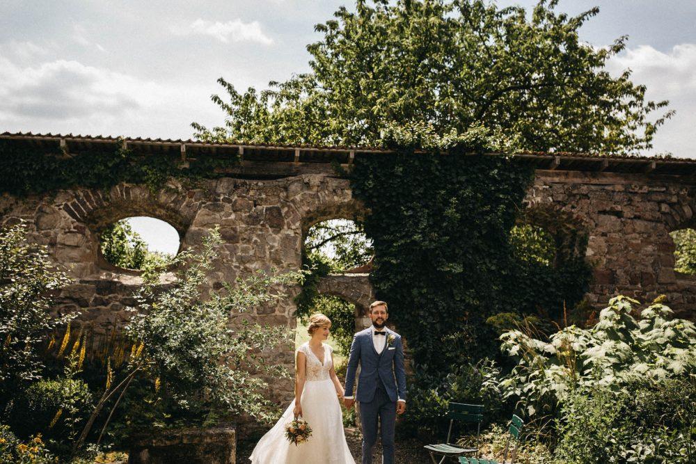 Brautpaar Händchen haltend im Garten des Wasserschloss Kleinbardorf | Raissa + Simon Fotografie