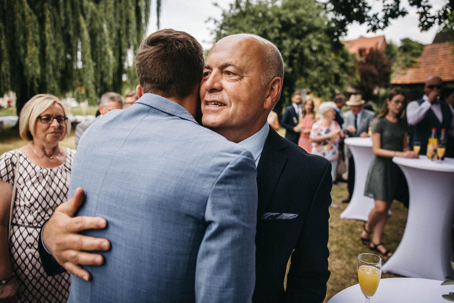 Hochzeitsgäste gratulieren dem Brautpaar im Garten des Wasserschlosses Kleinbardorf | Raissa + Simon Fotografie