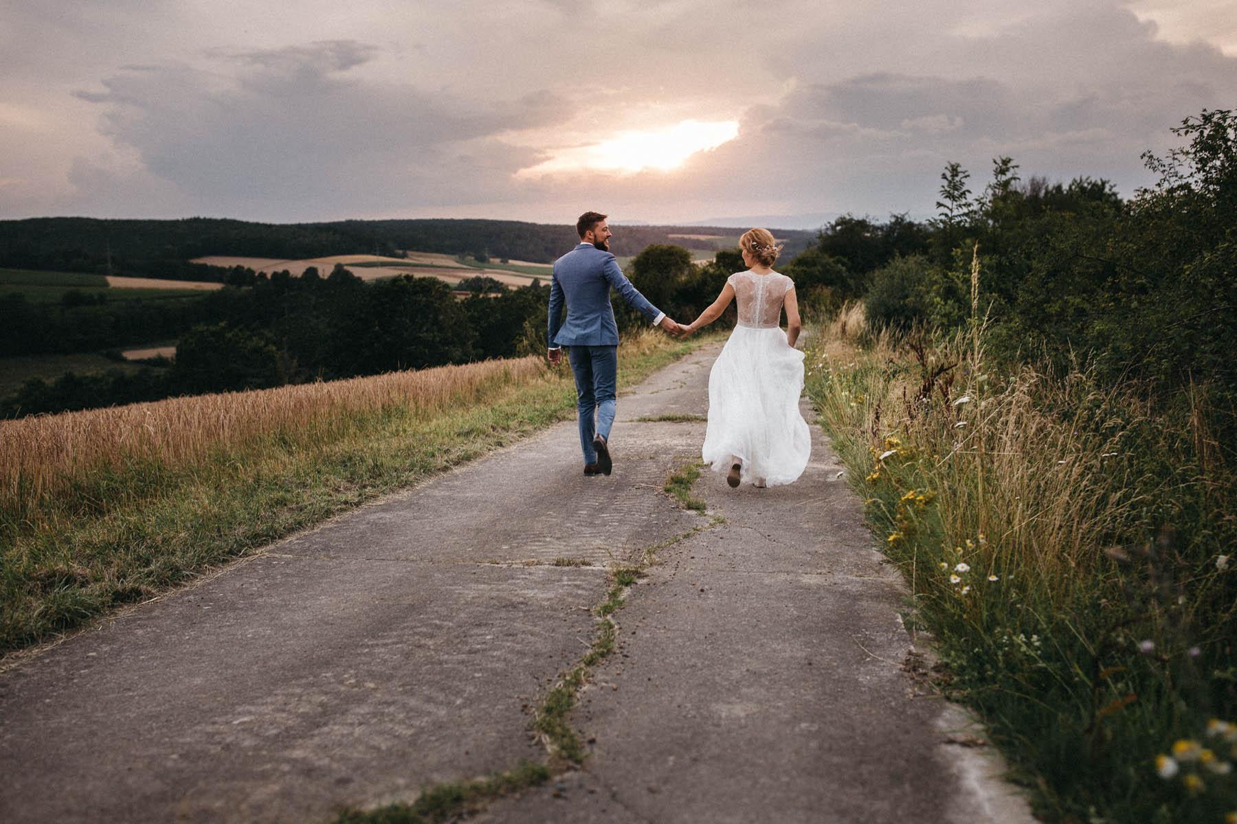 Brautpaar beim Sonnenuntergang auf einem Weg auf der Röhn in Unterfranken | Raissa + Simon Fotografie