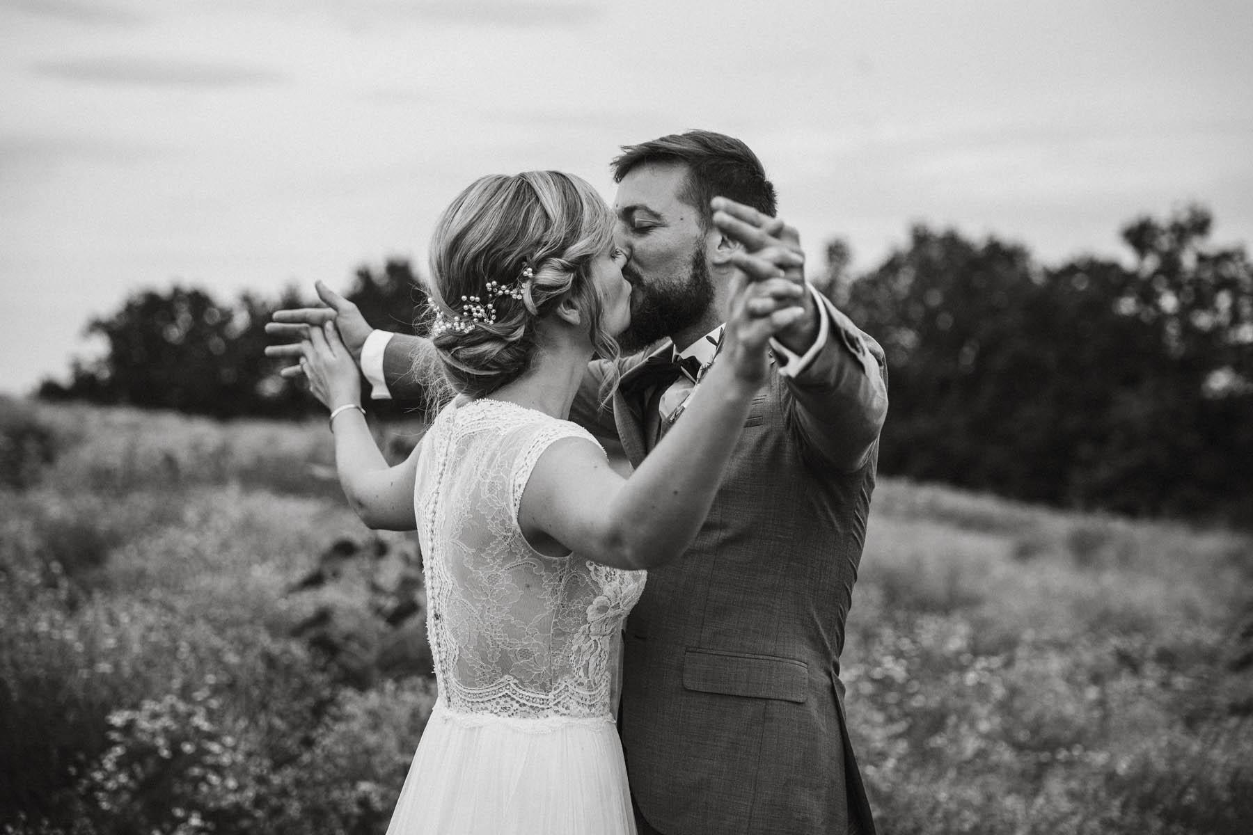 Brautpaar küsst sich in einer Blumenwiese auf der Röhn in Unterfranken | Raissa + Simon Fotografie