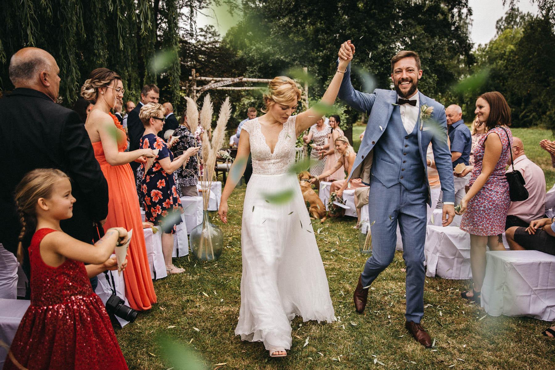 Brautpaar feiert den Auszug bei freier Trauung. Gäste werfen Blütenblätter | Raissa + Simon Fotografie
